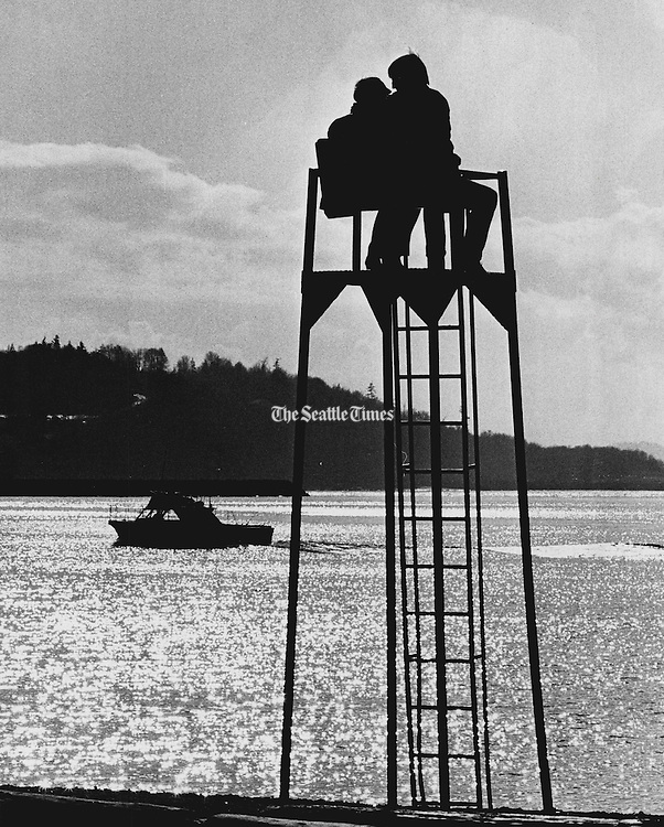 It takes but a little sun to attract a few to Seattle- area beaches. Mike Hendrickson and Gail MacKenzie occupied a life-guard tower to watch water traffic at Golden Gardens Park. (Josef Scaylea / The Seattle Times, 1971)