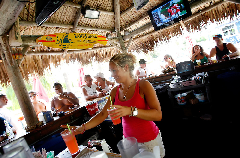 """SIESTA KEY, FL -- August 22, 2009 -- Bartender Jennifer O'Connell, or """"Bubbles"""" as she is known to patrons, serves up drinks in the tiki bar at Captain Curt's Crab & Oyster Bar on Siesta Key in Sarasota, Fla., on Saturday August 22, 2009.  Summer is becoming a more popular time to visit Siesta Key out of season with shorter lines, cheaper rates, and more room to plop a towel and umbrella down in said sand."""