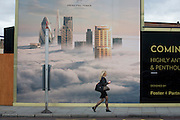 A woman walks beneath a property developer's billboard showing a large aerial image of London skyscrapers in low cloud.