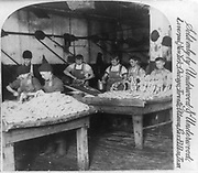 The sausage department, Armour's great packing house, Chicago, U.S.A.  Men and boys stuffing sausage skins at two tables.  photoprint on stereo card  c1893.