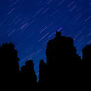 Fisher Towers silhouetted by the night sky and star trails of the moving earth near Moab, Utah.