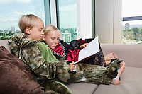 Siblings in dinosaur and vampire costumes reading picture book together on sofa bed at home