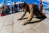 A Tibetan pilgrim prostrating himself repeatedly as he circumambulates through Barkhor Square and along The Barkhor (around the area of the Jokhang Temple), the most sacred temple in Tibet, Lhasa, Tibet, China.