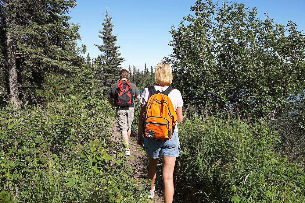USA, Alaska, couple walking along trail in forest