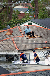 29 August, 2005. New Orleans, Louisiana.<br /> Hurricane Katrina hits New Orleans. Rescue workers frantically search for survivors in the rising flood waters of the 9th ward, bringing them to relevant safety on the elevated section of I-10. A man is rescued from his rooftop, having smashed his way out as flood waters rose.<br /> Photo; Charlie Varley.