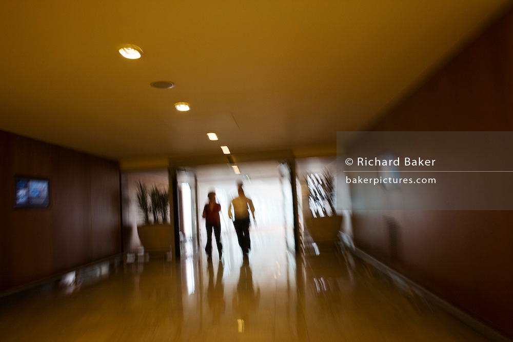 Two hotel guests head for exit in connecting corridor in Sofitel at Heathrow's terminal 5 hotel.