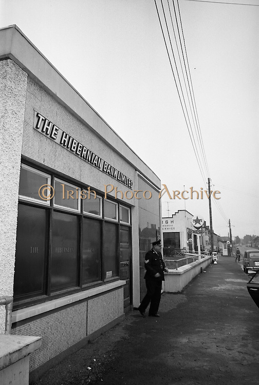Hibernian Bank sub-office at Dunshaughlin..1965..13.03.1965..03.13.1965..13th March 1965..The Hibernian Bank sub-office at Dunshaughlin, Co. Meath was broken into lat night, it has not yet been determined how much money the raiders managed to escape with...Image shows a Garda sergeant on duty outside the sub office of the Hibernian Bank which was broken into overnight.