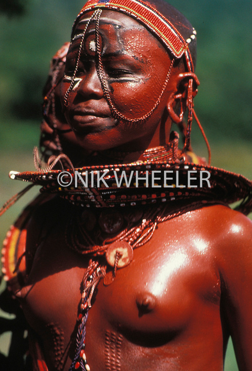 Bare breasted Masai girl dancer in traditional costume in the Masai Mara in Kenya, East Africa