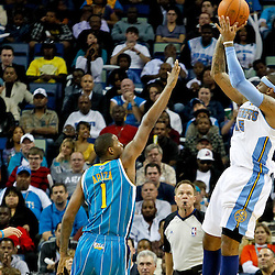 October 29, 2010; New Orleans, LA, USA; Denver Nuggets small forward Carmelo Anthony (15) shoots over New Orleans Hornets small forward Trevor Ariza (1) during the fourth quarter at the New Orleans Arena. The Hornets defeated the Nuggets 101-95.  Mandatory Credit: Derick E. Hingle