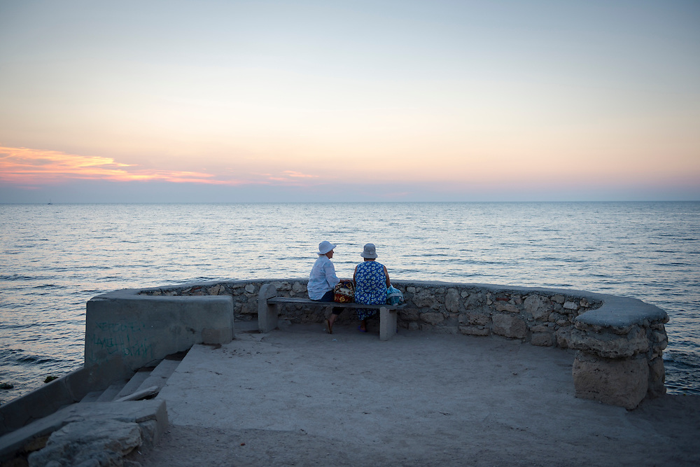 Two women sit on a bench at Khersones, looking over the Black Sea at sunset. Khersones is an ancient Greek colony founded approximately 2,500 years ago in the southwestern part of the Crimean Peninsula.