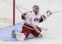 Oct 10; Newark, NJ, USA; Carolina Hurricanes goalie Cam Ward (30) makes a glove save during the third period at the Prudential Center. The Devils defeated the Hurricanes 4-2.