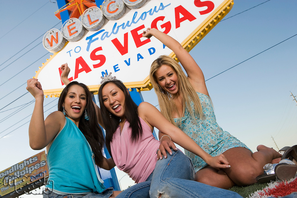 Three women in front of Las Vegas welcome sign, Nevada, USA