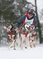 Keith Bryar of Moultonboro crests the final hill before crossing the finish line with a time to earn first place in the John H. Lyman Memorial Open Class race Sunday afternoon for the 82nd annual Laconia World Championship Sled Dog Derby.  (Karen Bobotas/for the Laconia Daily Sun)