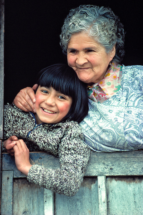 A Chilean woman hugs her granddaughther as they look from their doorway near Puerto Montt, Chile.