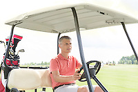 Middle-aged man driving cart at golf course