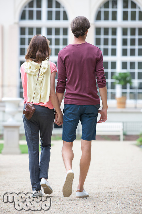 Full-length rear view of young couple walking against building