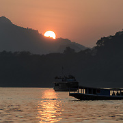 Boats out to watch the sunset on the Mekong River near Luang Prabang, Laos.