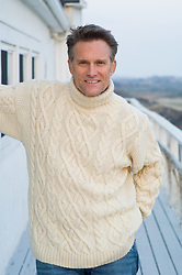 Good looking mature man in a white turtle neck sweater