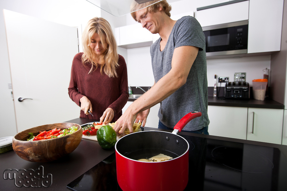 Caucasian couple cooking pasta together in kitchen