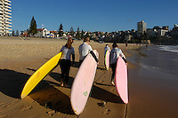 Early morning young women go surfing on Manly beach, Sydney, NSW, Australia.