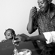 Burundian refugee Angelique Barakamfitiye eats at the dinning room table with her daughter Delphine Nibigira, 2, and her husband Jean-de Dieu Havyalimana in their own apartment. The family dining room experience was a new one for the family. The furniture was donated by several christian groups.