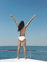 Young woman in bikini standing on bow of yacht outstretching arms back view