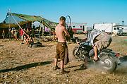 Men on motorbike in dust, BulgariaTek, Bulgaria, August 2011