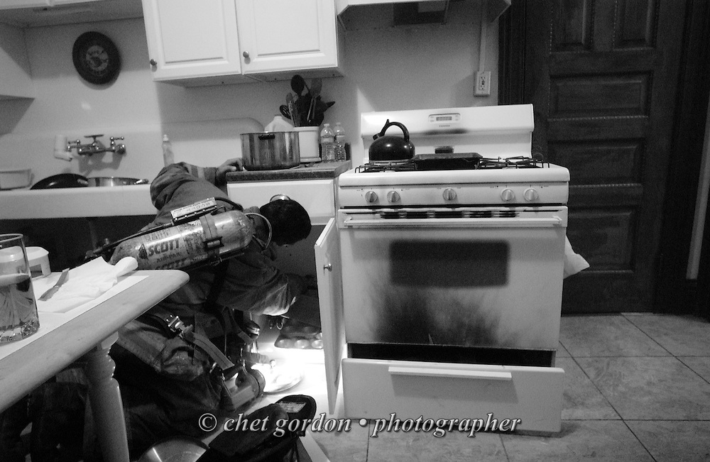 A Newburgh firefighter shuts off the natural gas line to a stove after firefighters responded to a kitchen fire in Newburgh, NY on Wednesday evening, October 5, 2011.  © www.chetgordon.com/blog