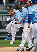 Kansas City Royals' Alex Gordon, left, is lifted up by his teammates after his game-winning hit in the 10th inning of a baseball game against the Chicago White Sox at Kauffman Stadium in Kansas City, Mo., Sunday, May 5, 2013.  (AP Photo/Colin E. Braley).