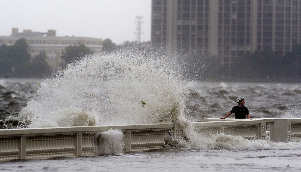 An unidentified boy stands along the balustrade as waves crash onto Bayhore Boulevard Sunday, June 24, 2012 in Tampa. Hard rain and wind pelted the Tampa Bay area Sunday as Tropical Storm Debby headed toward the coast of Louisiana.