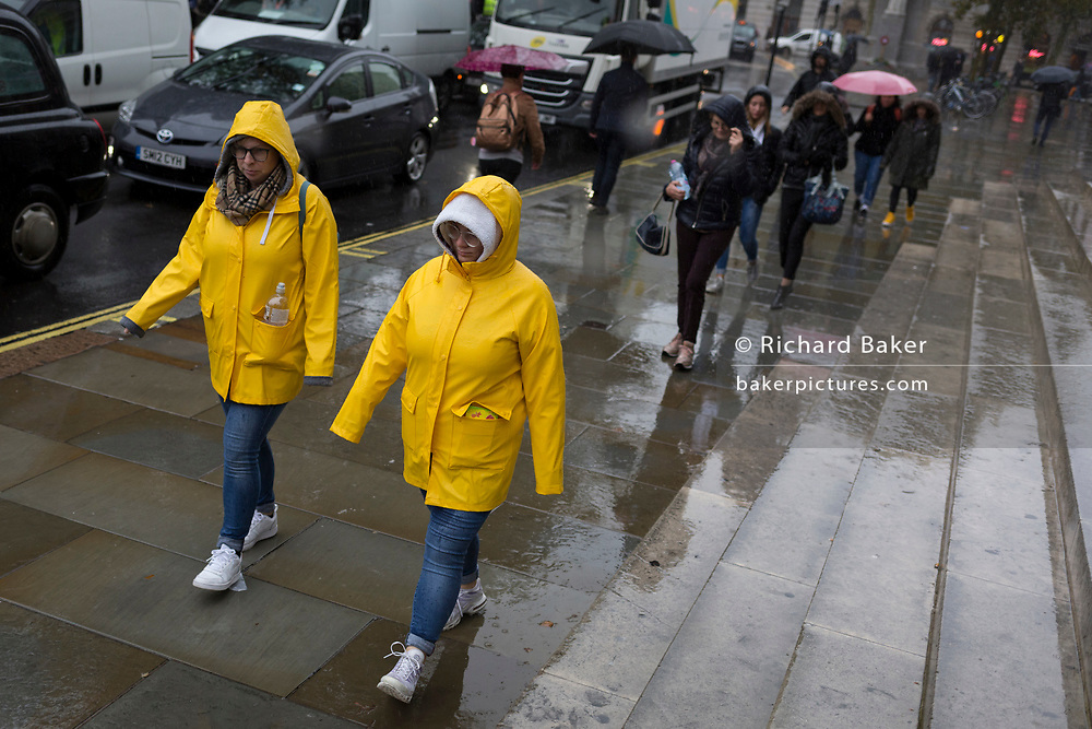Identically-dressed visitors to the capital endure heavy rainfall on an autumn afternoon in Trafalgar Square, on 24th October 2019, in Westminster, London, England.