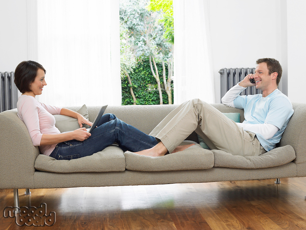 Couple reclining on couch using laptop and cell phone