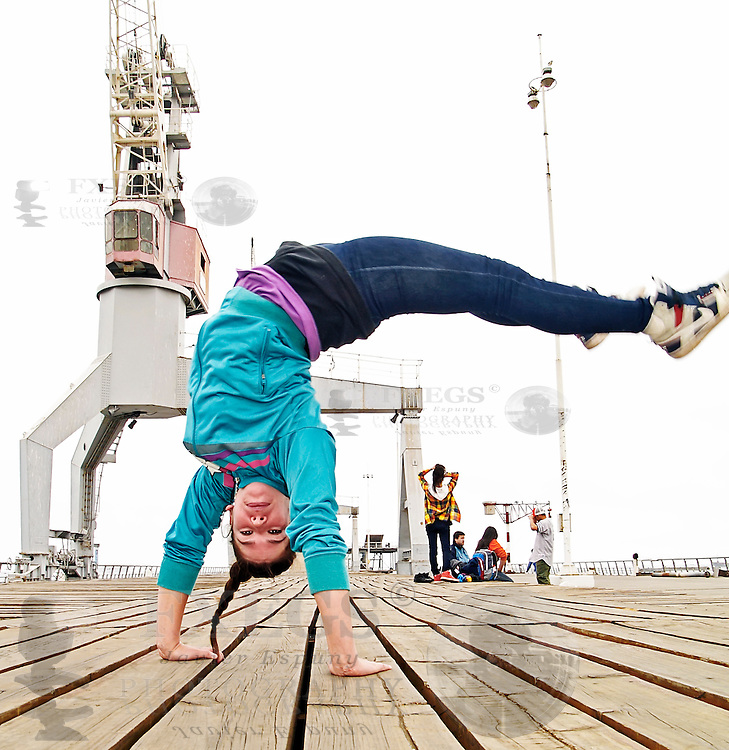 Young female breakdancing in the middle of a jump