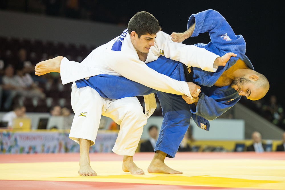 Fernando Ibanez (L) of Ecuador tries to avoid being thrown by Augusto Miranda of Puerto Rico during their bronze medal contest in the men's judo 73kg class at the 2015 Pan American Games in Toronto, Canada, July 12,  2015.   AFP PHOTO/GEOFF ROBINS