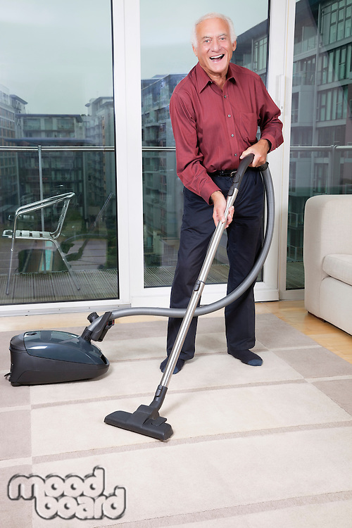 Portrait of happy elderly man cleaning rug with vacuum cleaner at home