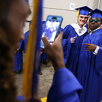 Tueplo graduating senior Iggi Free, takes a picture of his fclassmates Chael Williams and McKenzie Richardson as they wait back stage at the BansorpSouth Arena prior to the start Tupelo High School graduation ceremony Friday night in Tupelo.