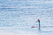 A lone man stand up paddling on the ocean in Hawaii.