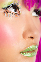 Extreme close-up of young funky woman's face with false eyelashes and green lipstick