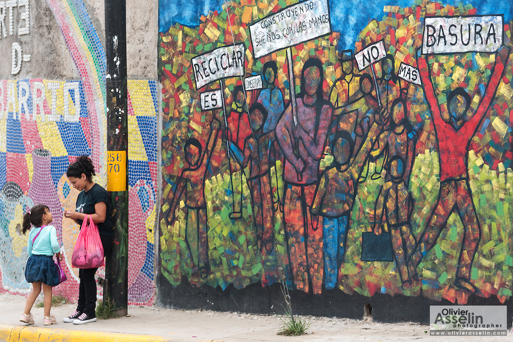 A woman and a girl stand next to a large wall painting in the town of Valle de Angeles, Honduras on Friday April 26, 2013.