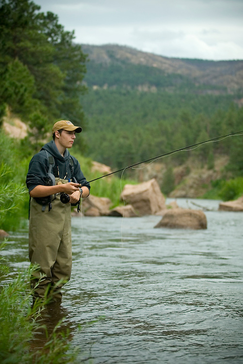 A fly fisherman presents his fly to rising brown trout on the South Platte River near Deckers, CO.