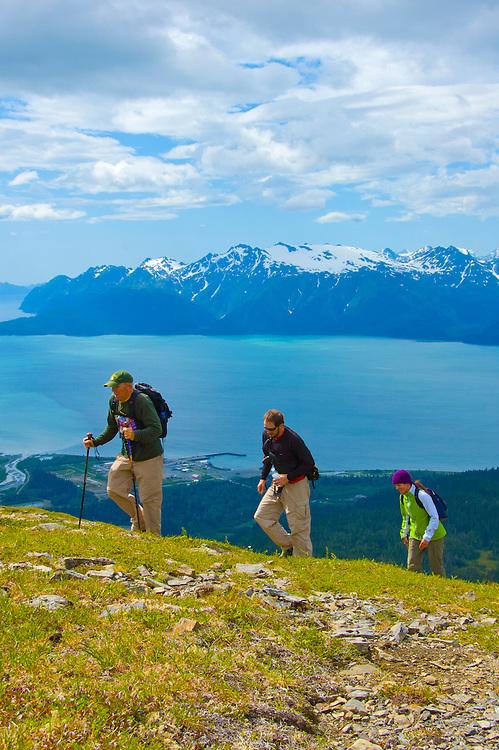 Three hikers enjoying the beautiful day and the challenge of hiking Mt. Alice near Seward, AK.