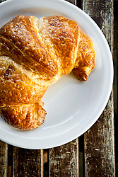 Golden brown croissant on white plate