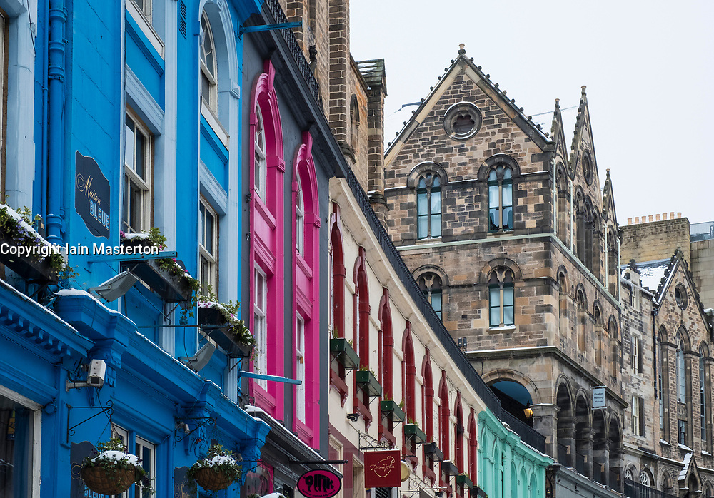 View of colourful shop fronts historic Victoria Street in Edinburgh Old Town after heavy snow, Scotland, United Kingdom