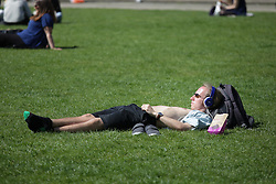 © Licensed to London News Pictures. 21/04/2015. Bristol, Avon, UK. A man sunbathing and enjoying the warm weather on College Green in Bristol today, 21st April 2015. The south west of England is set for more warm temperatures and plenty of sunshine today. Photo credit : Rob Arnold/LNP