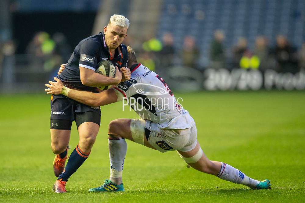 Matt Scott (#12) of Edinburgh Rugby is tackled by Kieran Treadwell (#5) of Ulster Rugby during the Guinness Pro 14 2018_19 match between Edinburgh Rugby and Ulster Rugby at the BT Murrayfield Stadium, Edinburgh, Scotland on 12 April 2019.