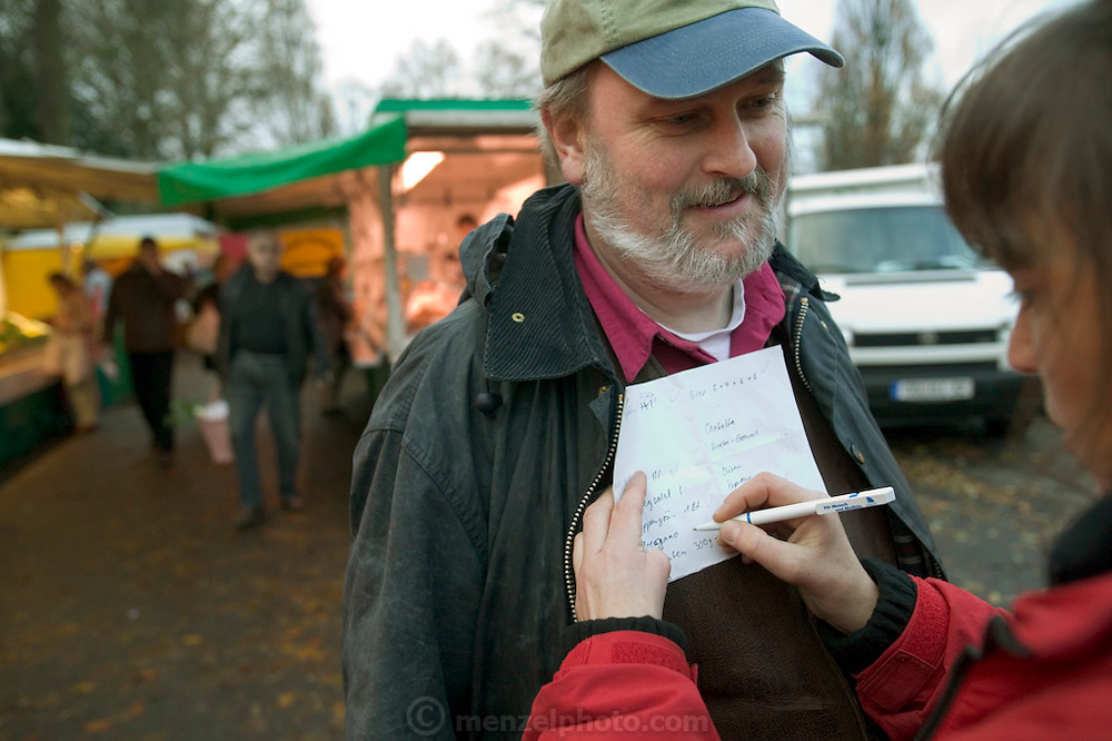 (MODEL RELEASED IMAGE). At the outdoor Friday market in their tidy community of Bargteheide, Germany, Susanne Melander steadies her shopping list on Jörg's chest as she checks off purchases. Hungry Planet: What the World Eats (p. 136).