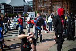 © Licensed to London News Pictures . 30/07/2017 . Manchester , UK . A man carries another dressed as Spiderman in the crowds outside the venue . Cosplayers, families and guests at Comic Con at the Manchester Central Convention Centre . Photo credit : Joel Goodman/LNP