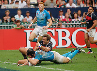 HONG KONG, HONG KONG : Rob Vickerman of England goes for the score as Nick Hewson of Hong Kong tries to bring him down, in England's  42-7 win in the Bowl Final, at the Hong Kong Rugby Sevens, shown in Hong Kong on Sunday, 24 March, 2013.
