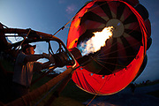 Hot air balloon pilot heating his balloon for an evening's glow activity heating