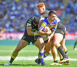 Leeds Rhinos' Tom Briscoe is tackled by Warrington Wolves' Ben Murdoch-Masila and Harvey Livett during the Ladbrokes Challenge Cup Semi Final match at the Macron Stadium, Bolton.